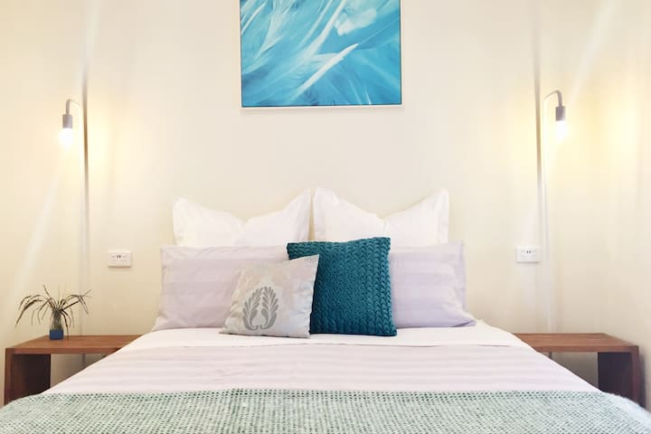 Comfortable Queen bed, phone charger points, bedside tables with lamps, comfortable linens, big pillows, and hanging rack and luggage stand.
