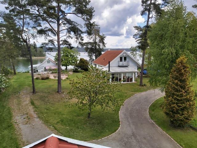 Hus på Bråvikens strand med utespabad och uterum.