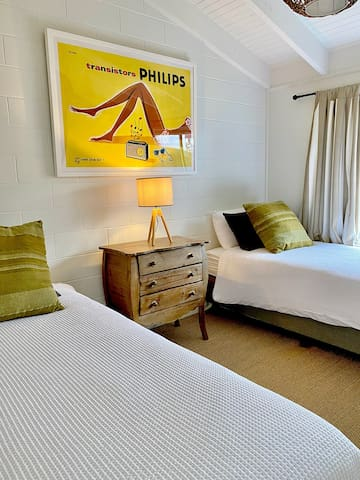 Our second bedroom is fun and comfortable. Perfect for two kids or join the beds together for a couple. * We have swapped out the old chest of drawers for a low table since this photo was taken.