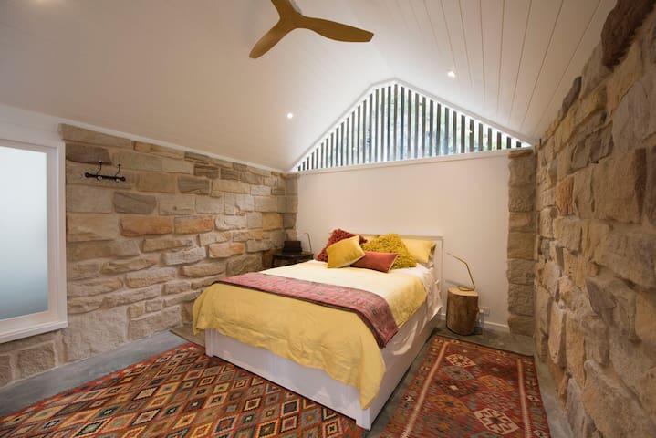 the original sandstone garage has been converted into a comfortable bedroom