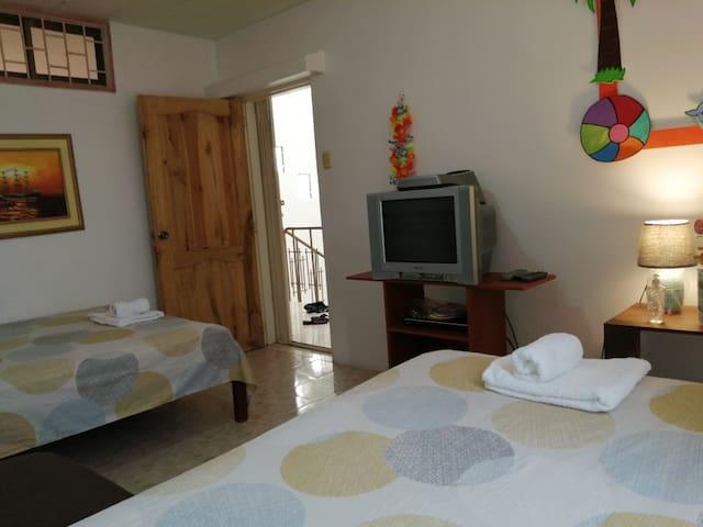 Dormitorio 3, amplio con 1 cama de 1 1/2 y 2 plazas, con su respectivo A/C y vista al área social. Tenemos un Photobook y collares hawaianos.