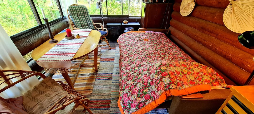 Sleeping on the porch is possible.   But bring your own sheets or a sleeping bag. It's 105 cm wide. Two people who love each other should do just fine.  There's a heat lamp, and an electric stove if it get's chilly.