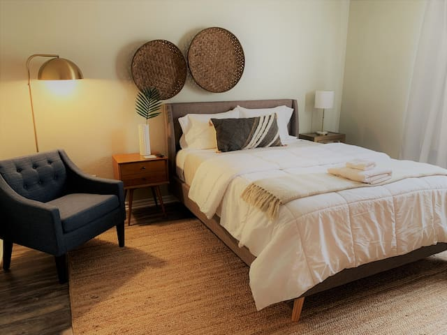 Bright, light and airy master bedroom with extra seating and two nightstands.