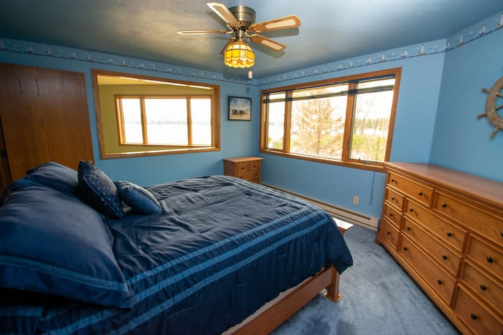 First of three bedrooms has a queen bed and water view
