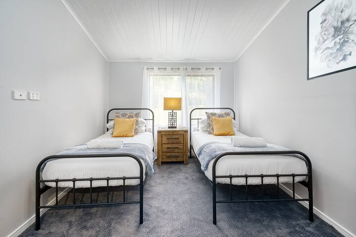 The cosy third bedroom has 2 x single beds and a large chest of drawers.
