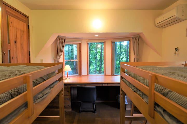 ゲストルームA 緑に面した大きな楕円出窓から見える景色はまるで森の中にいるようです。鳥のさえずりで目覚めるリッチな朝をお楽しみください。 エアコン・加湿器・換気扇・懐中電灯・アルコールスプレー設置してございます。