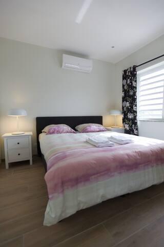 Onze comfortabele ruime master bedroom is uitgerust met airco voor een koele nachtrust. Ook kan je hier lekker tv kijken op bed