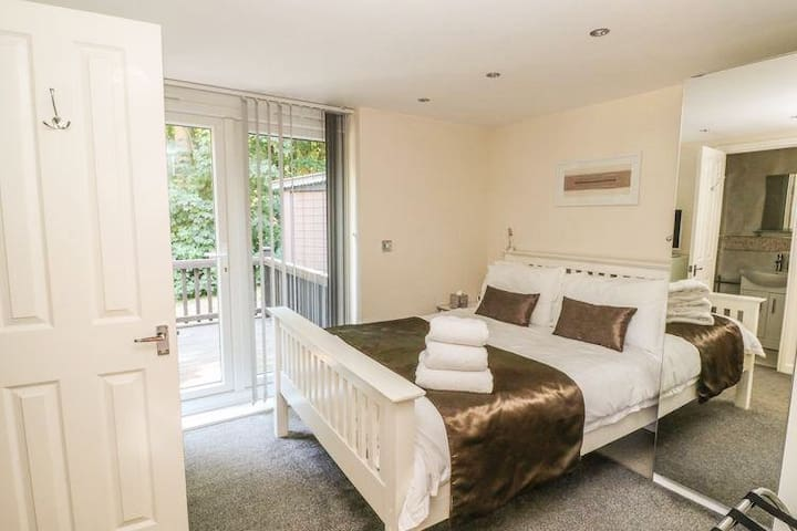 Bedroom has a double bed with memory foam mattress and Egyptian cotton sheets. Wardrobe with wooden hangers and large chest of drawers. Patio doors lead out into private decking area with views into surrounding woodland.