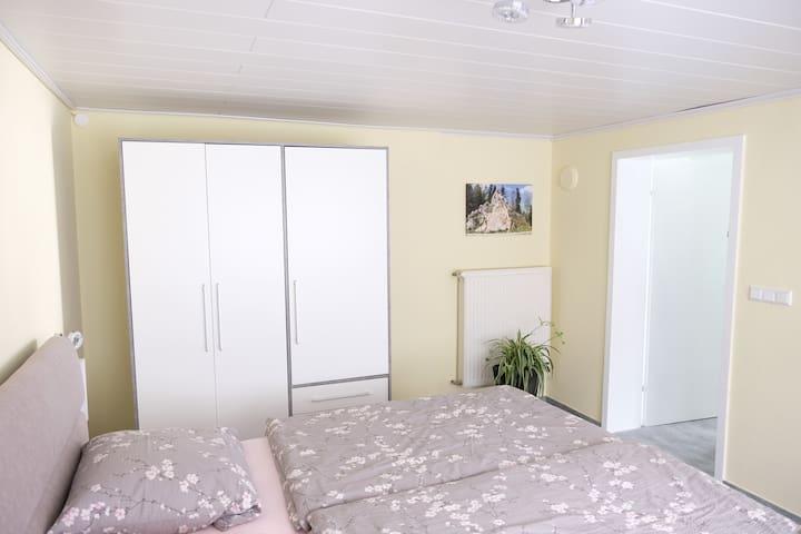 Schlafzimmer mit geräumigem Schrank, Doppel Bett, Tisch mit zwei Stühlen und Fenster   Sleeping room with a wardrobe, double bed, table and two chairs, window