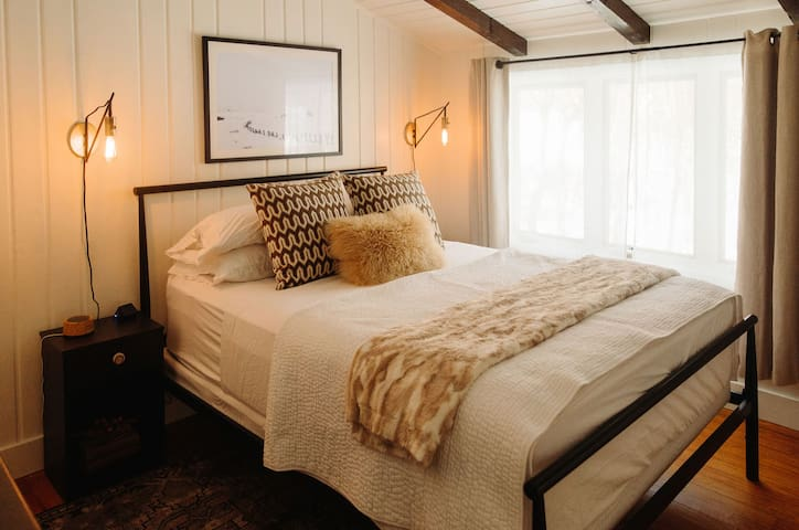 """The master bedroom with a WinkBed, the handmade luxury hybrid queen mattress, quality linens and pillows, a 43"""" flatscreen TV and light dimming curtains.  Photo by Rainstorm Photo"""