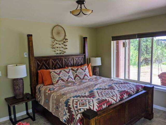 Master bedroom with bathroom walk in shower, king size bed and a Smart T.V.  View of Pikes Peak.