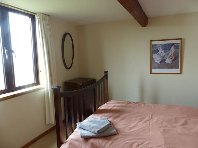 Double bedroom with wardrobe and chest of drawers.