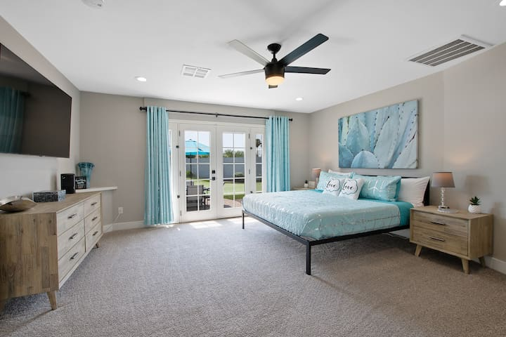 """Master Bedroom #2 looking out to Sitting area and Putting Green. 65"""" 4K TV with Direct TV"""