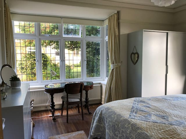 Huge wardrobe, writing desk in bay window towards garden