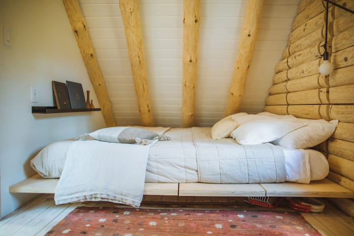 The loft bedroom has a California king Casper mattress and is tucked into the shape of the house.