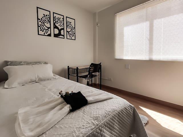 Quarto solteiro com cama confortável e mesa para laptop ou tablet.