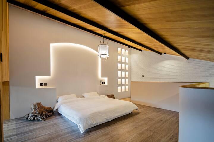 设计师在卧室床头墙壁上做了内嵌式拱顶设计,柔软的曲线轮廓给人以视觉上的延伸之感
