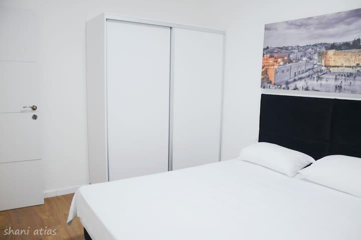 חדר שינה #1 - סוויטת הורים - מיטה זוגית + ארון בגדים מודרני + חדר מקלחת שירותים צמוד .