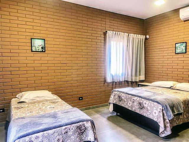 """Confortável suíte com 1 cama de casal e 1 de solteiro com cama auxiliar. Possui ar-condicionado e local para guardar roupas no formato de """"armário de hotel."""
