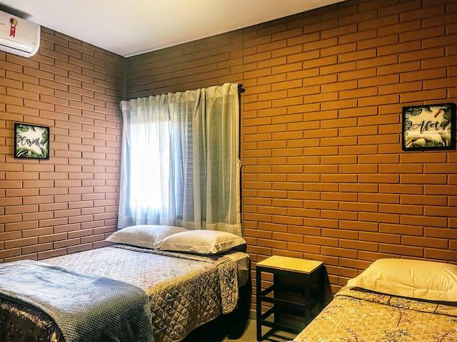 """Quarto com 1 cama de casal e 1 de solteiro com cama auxiliar. Possui ar-condicionado e local para guardar roupas no formato de """"armário de hotel""""."""