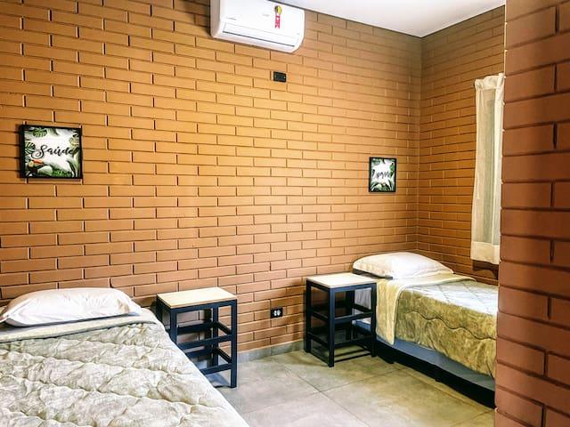 """Quarto super confortável com 2 camas de solteiro e 2 camas auxiliares. Possui ar-condicionado e local para guardar roupas no formato de """"armário de hotel""""."""