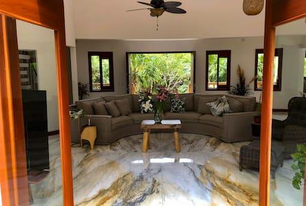 This is the grand entrance which can also be left open. With the big double doors open it complements the 3 big curved doors open at the front. This gives a very unique feeling as the breeze from the ocean flows  through property.