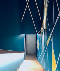 L'ingresso esterno è visibile grazie a due luci a lama verticale che delimitano il portone. All'interno del B&B la scala blu completamente illuminata vi accompagna al primo piano dove sarà possibile accedere alle tre camere.