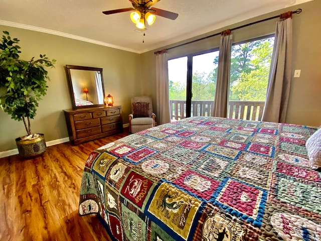 """""""Lantern Glow"""" main bedroom offers warm outdoor theme bedding and a cozy balcony view."""