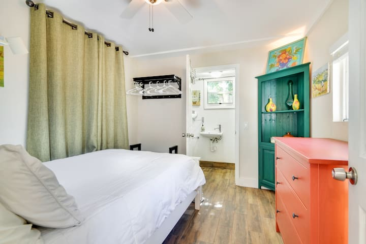 This bedroom has a full size bed and a private bathroom with a shower.