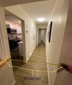 The hallway is over 3 feet wide, and free of carpet, furniture or other obstacles.
