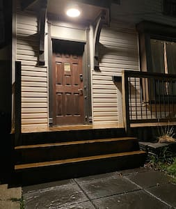 This is the front entrance way to the home. There are 3 stairs. The area is lit by street lamps, and an outdoor light fixture.