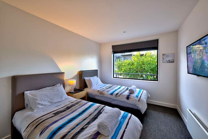 The third bedroom is spacious with a TV