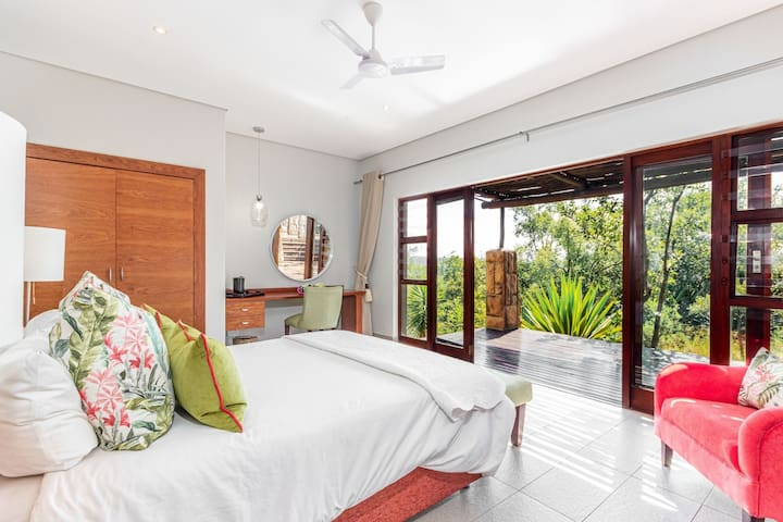 The pink room, equipped with a king size bed and a full en-suite bathroom, as well as an outdoor shower. Large doors open onto a covered deck and bushveld views. All bedrooms are detached from the home for ultimate peace and privacy.