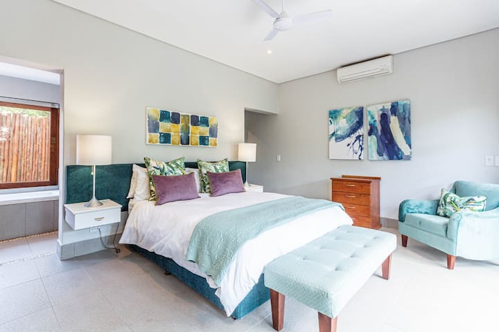 The turquoise room, equipped with a king size bed and a full en-suite bathroom, as well as an outdoor shower. Large doors open onto a covered deck and bushveld views. All bedrooms are detached from the home for ultimate peace and privacy.