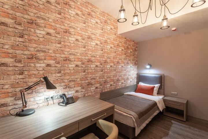 спальня с одной кроватью и рабочим столом