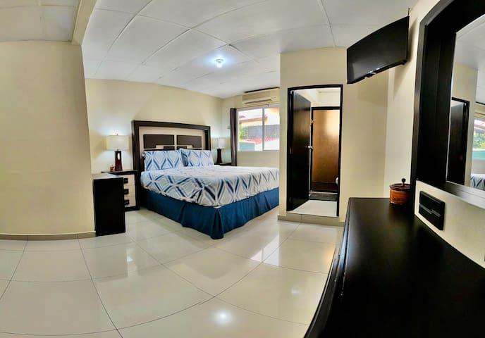 Habitación principal, amplia, con sofa cama, aire acondicionado y baño privado, dos closets:  Un closet amplio y un walk-in closet con variedad de gavetas para la ropa. Smart TV con cable incluido.  Con vista a la piscina.