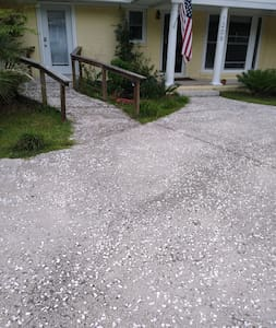 You'll park at your door on a flat concrete and she'll drive and walk up a short ramp to your door. Ramp is approximately 45 inches wide and rises 14 inches over 14 feet.