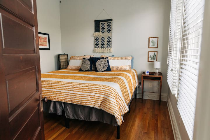 Bedroom features a king size bed with large windows overlooking downtown Frankfort.