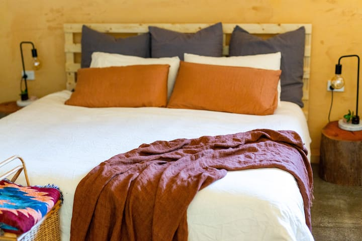 Rustic King Bed surrounded by artisan clay walls and views to the rainforest