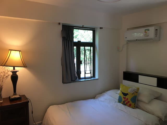 Downstairs- first guest room with a double bed and a desk overlooking a big old tree