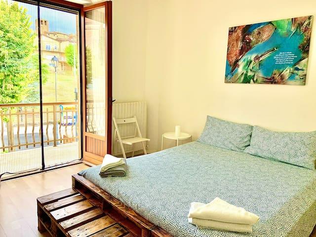Stanza OVEST con letto matrimoniale e balcone privato con vista sul borgo/torre orologio