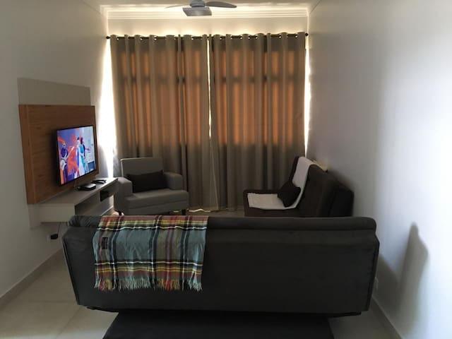 Sala muito bem iluminada e arejada, com cortinas, possui ventilador de teto e uma Smart Tv com TV a cabo, ambos sofás, são sofá cama.