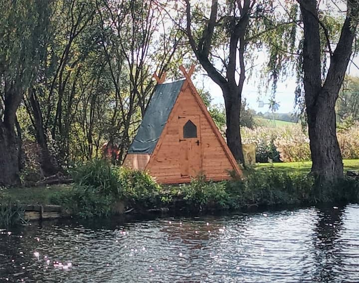 Twin-bed wooden tipi next to mature fishing pond