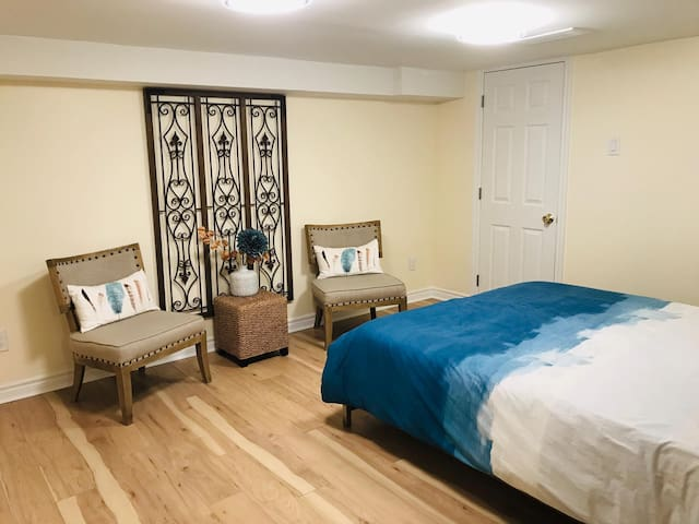 Very spacious master bedroom with a queen bed, sitting area and modern decor!