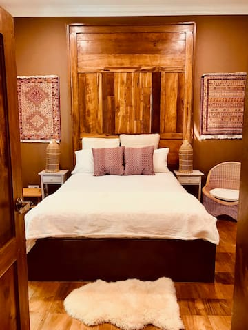 Persian bedroom has an all teak tile floor with teakwood wall panel and doors and is adorned with three Persian woven wall hangings. Ground floor.