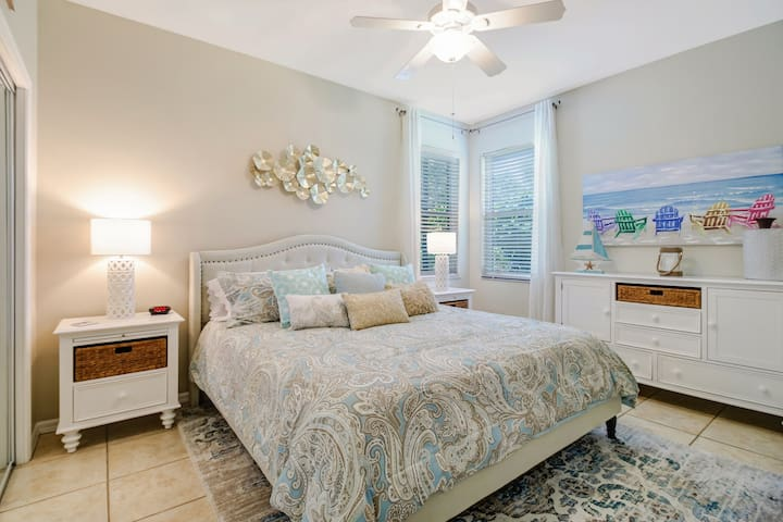 Light and airy guest bedroom with queen size bed, TV and closet space.