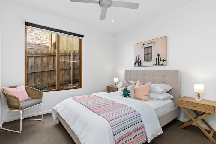 Spacious Queen bedroom with ceiling fan, beautifully appointed with hotel quality sheets and bath towels.