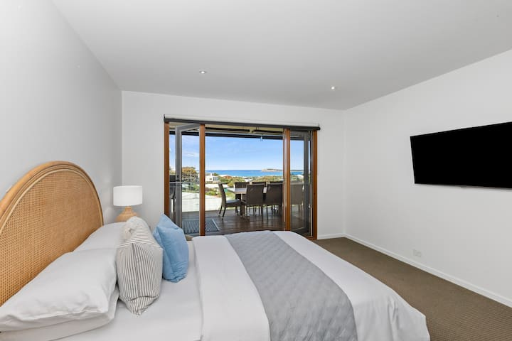 The King size Master bedroom is zoned for privacy on the top floor, embracing beautiful Bluff and ocean views with French doors to the deck. A walk-through robe leads to an ensuite with spa sanctuary vibes.