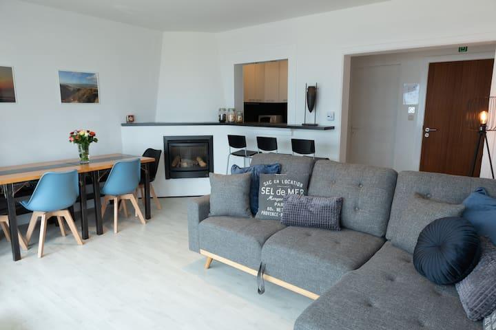 De woonruimte is voorzien van een eettafel met 4 stoelen en een zitbank. Een ontbijtbar en een knusse zetel. Je hebt rechtstreeks toegang tot de keuken.