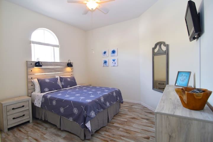 Beautiful queen bedroom with new furnishings throughout, flat screen SMART TV, ceiling fan